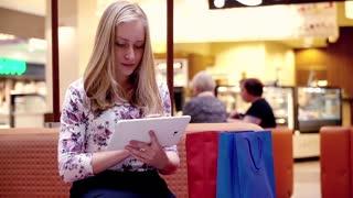 Cute teenage using tablet computer at shopping mall