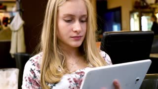 Cute teenager using tablet computer in cafe