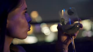 Face of beautiful pensive woman drinking white wine at night, 4K