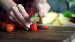 Female hands  cutting tomato on wooden board  super slow motion
