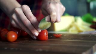 Female hands  cutting tomato on wooden board