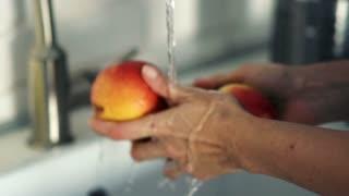 Female hands washing apple under water in sink