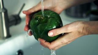 Female hands washing pepper under water in sink, super slow motion