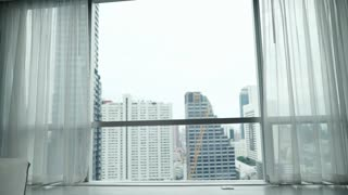 Handsome man in bathrobe admire city standing by the window, 4K
