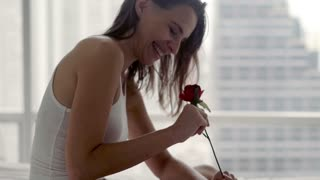 Happy, beautiful woman smelling rose lying on the bed at home