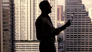 Happy businessman reading good news on tablet computer standing by the window, super slow motion