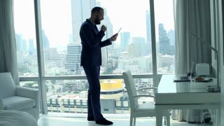 Happy businessman reading good news on tablet computer standing by window, super slow motion