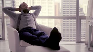 Happy businessman relaxing on armchair at home, 4K