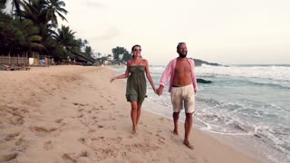 Happy couple walking on the beach, super slow motion
