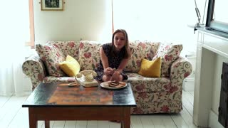 Happy, funny woman eating tasty cookies on sofa