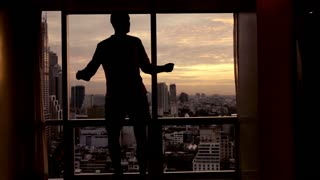Happy man dancing close to the window, super slow motion