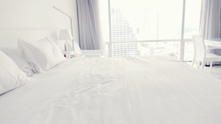 Happy man falling on bed at home, super slow motion