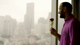 Happy man in love smelling rose close to the window, 4K