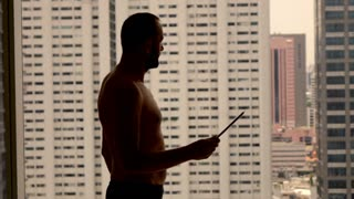 Happy man reading good news on tablet computer standing by window in the city, super slow motion
