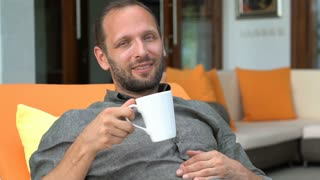 Happy man talking to camera and drinking tea lying on sunbed at home