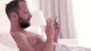 Happy man watching movie on smartphone lying on bed