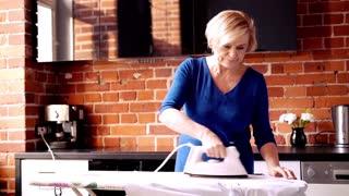 Happy, senior woman ironing shirt at home