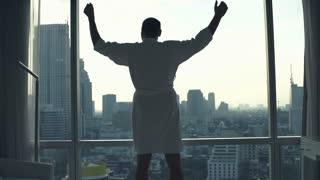 Happy, successful man in bathrobe raising arms, power symbol in hotel room, super slow motion
