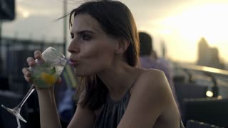Happy woman drinking cocktail in cafe in the city, 4K