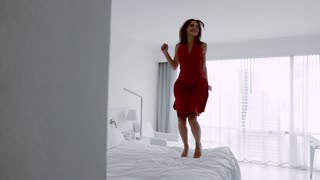 Happy, young, elegant woman jumping on bed, super slow motion