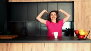 Happy, young woman relaxing and drinking coffee in kitchen in the morning