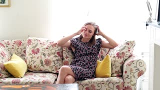 Happy, young woman relaxing on sofa at home