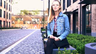 Impatient, pretty woman waiting for someone while sitting on the bench