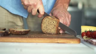 Man hands  slicing wholemeal bread