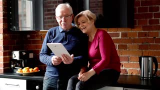 Mature couple chatting on tablet standing in the kitchen