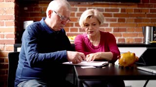 Mature couple counting bills in the kitchen