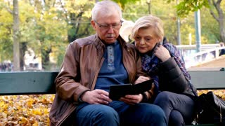 Mature couple reading on a bench in the city park