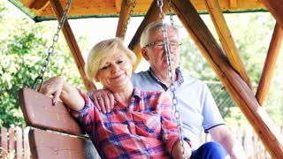 Mature couple relaxing on the swing in the garden