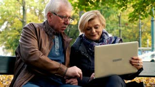 Mature couple sitting on a bench and using laptop in the city
