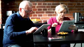 Mature couple sitting with tablet and newspapers in the kitchen
