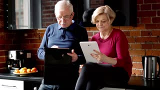 Mature couple sitting with tablet in the kitchen