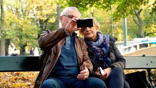 Mature couple taking selfie photo sitting on a bench park