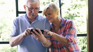 Mature couple talking and using smartphone sitting by the window
