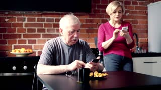 Mature couple talking and using smartphone sitting in the kitchen