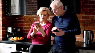 Mature couple talking and using smartphone standing in the kitchen
