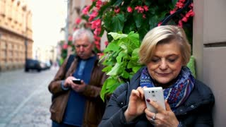 Mature couple using smartphone in the city