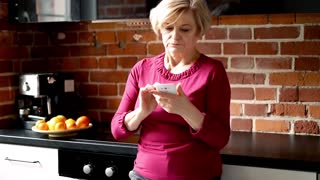 Mature couple using smartphone standing in the kitchen
