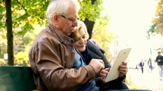 Mature couple using tablet computer sitting on a bench in the city park