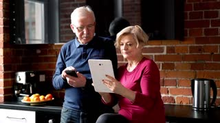 Mature couple with tablet computer standing in the kitchen