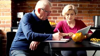 Mature, worried couple counting bills in the kitchen