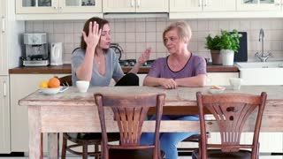 Mother and her adult daughter fighting in the kitchen