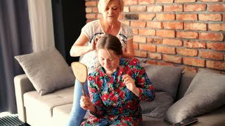 Mother combing hair her daughter on sofa at home