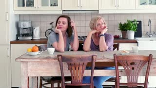 Offended mother and her adult daughter sitting in the kitchen