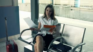 Overwhelmed, sad businesswoman by too much paperwork sitting at the train station