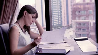 Overwhelmed, sad businesswoman with documents sitting in the office