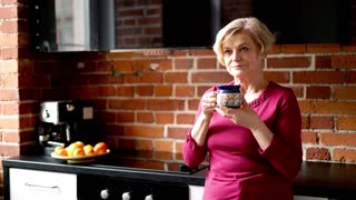 Portrait of beautiful, senior woman drinking tea and relaxing in the kitchen